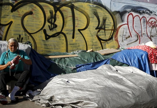 Woman sits outside tent on Skid Row in downtown Los Angeles