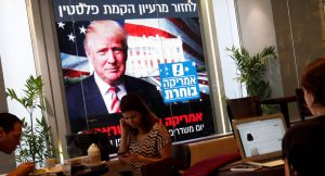 People dine at a Tel Aviv coffee shop Nov. 9 as an image of President-elect Donald Trump is displayed on a monitor. (CNS photo/Baz Ratner, Reuters) See ELECTION-TRUMP-REACTION Nov. 9, 2016.
