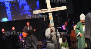 "An altar server carries a cross bearing the words ""cristo migrante"" (Spanish for ""migrant Christ"") and adorned with barbed wire that was found near the US-Mexico border, during a Spanish-language mass focusing on immigrants, exiles and refugees during the four-day 2017 Religious Education Congress in Anaheim, California, February 25, 2017. REUTERS/Andrew Cullen"